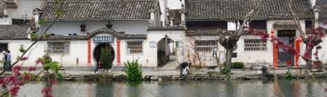 Hongcun village man washing in pond by Kevin Earl