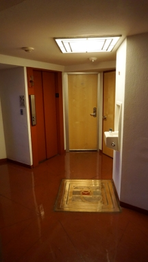 central area surrounded by elevators and rooms with HC Price Co. logo on floor medallion